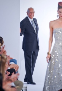 de la Renta on the runway watching one of his dresses.
